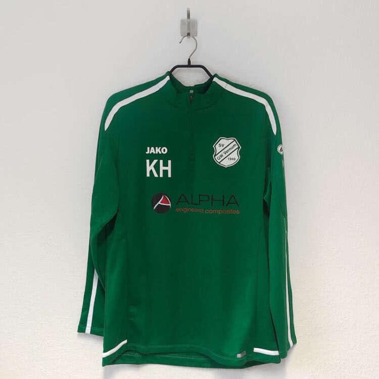 Das grüne Training Top mit Logo und Werbung auf der Brust