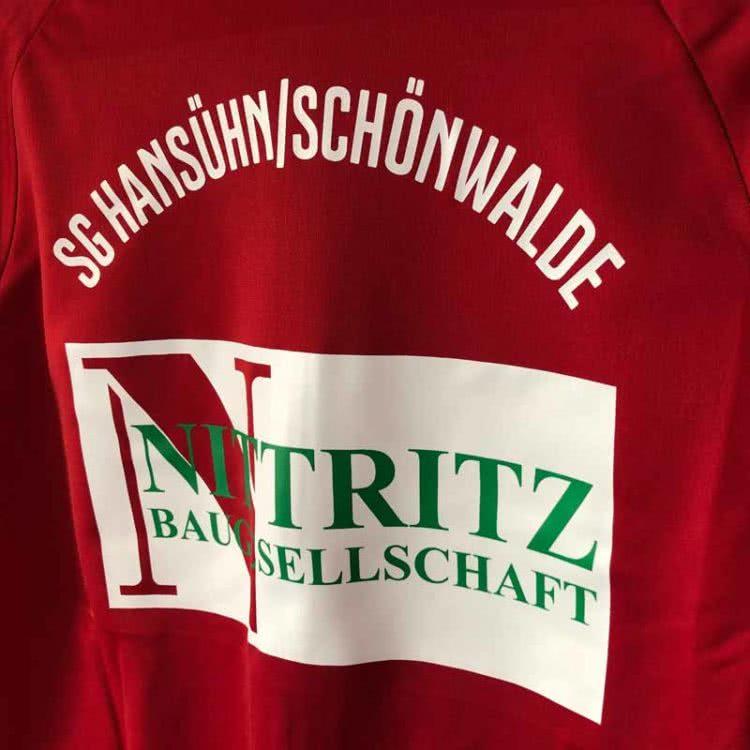 die adidas Polyesterjacke mit Vereinsnamen und Werbung der SG Hansühn Schönwalde