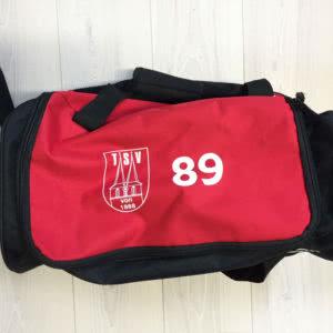 Die Sporttasche mit Druck des Vereinslogos und der Nummer